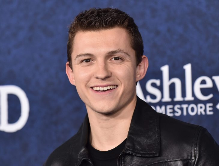 The actor Tom Holland smiling in the center of the photo with the background blurred.