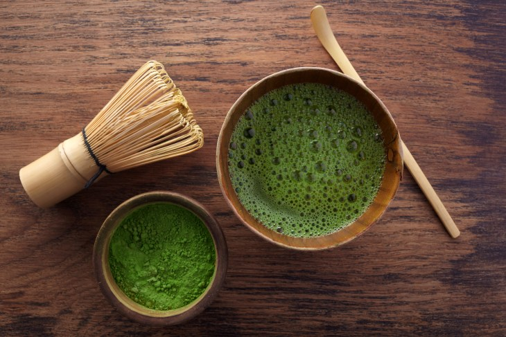 A glass of matcha with the powder in a bowl on the side with the whisk.