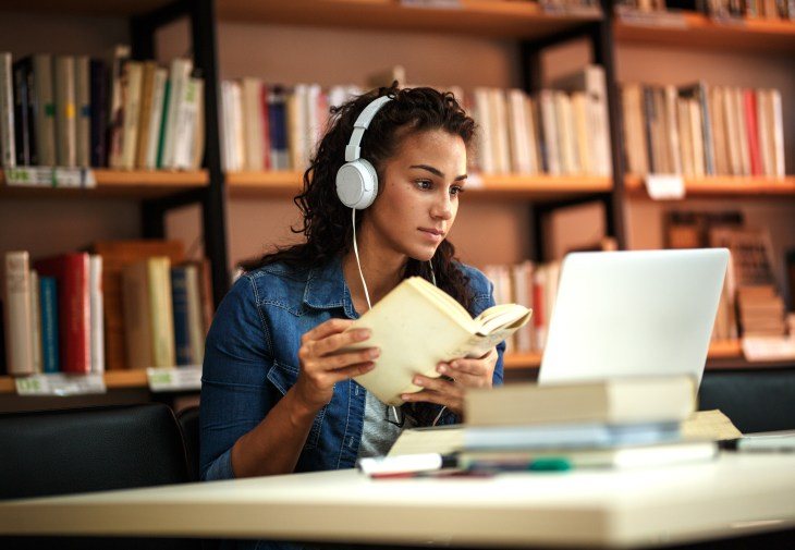 A girl in a library doing work on a computer and a book.