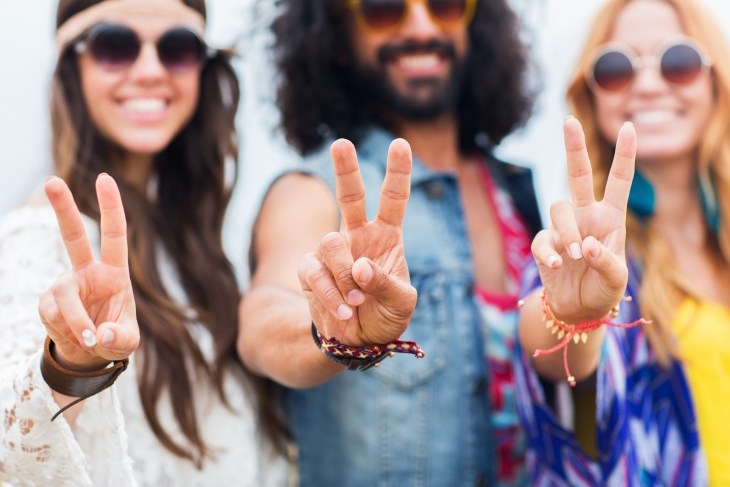 Three people dressed as hippies holding up peace signs.