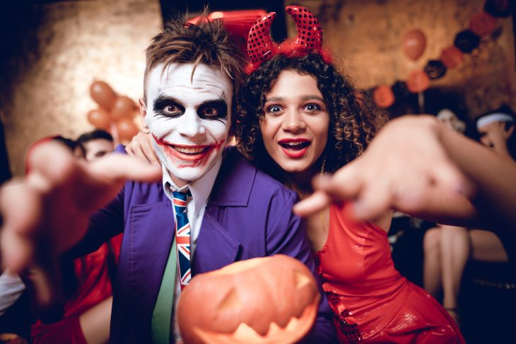 A man dressed as the joker and a woman dressed as a devil.