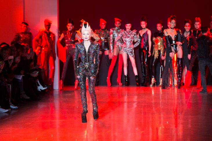 Daphne Guinness walking along the catwalk of her completed fashion show with models wearing her clothes out of focus behind her.