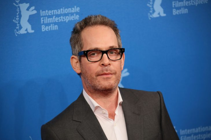 Tom Hollander wearing suit and glasses standing in front of blue backdrop.
