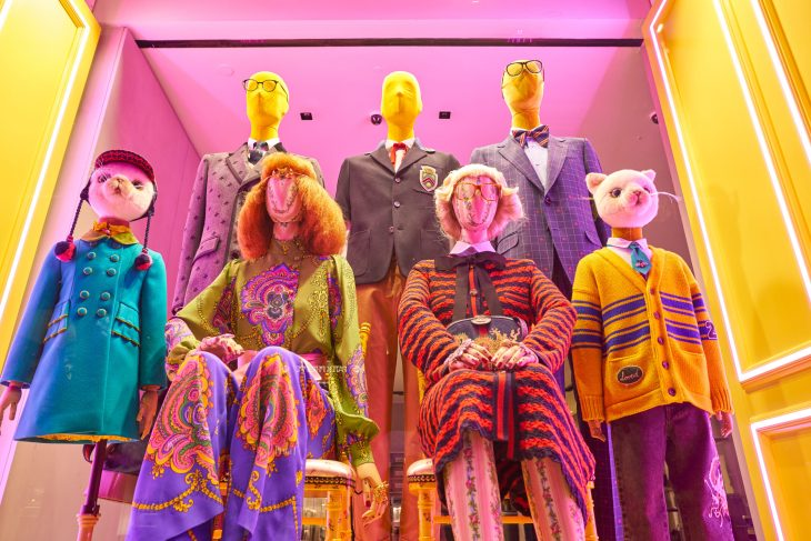 Gucci window display featuring two women in bright outfits, two animal mannequins in children's clothes on either side of them and three mannequins in structured suits behind them. The lighting is extremely bright neon and colorful.