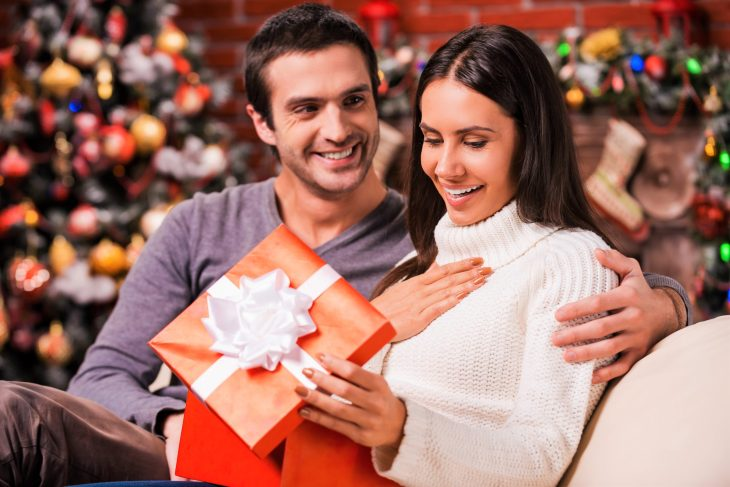 Beautiful young woman opening a gift box and smiling while her boyfriend sitting close to her on the couch with Christmas decoration in the background