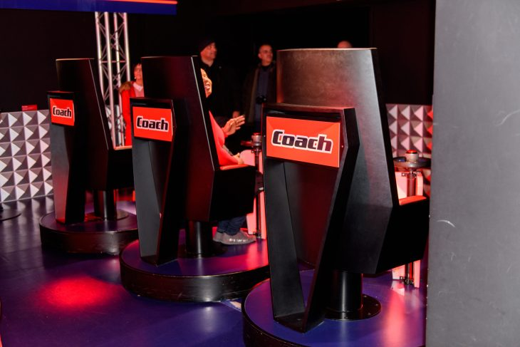 Four chairs are lined in the picture that shows the logo of The Voice on each chair. The picture was taken place in the room were the performers performed.