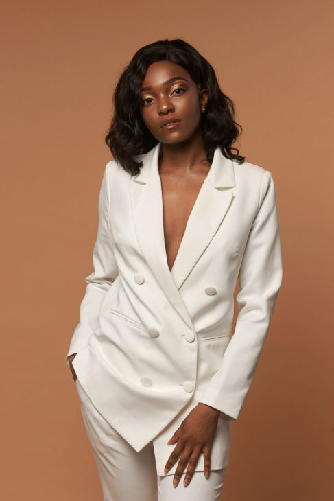 A Black female wears a full white suit in a brown background.