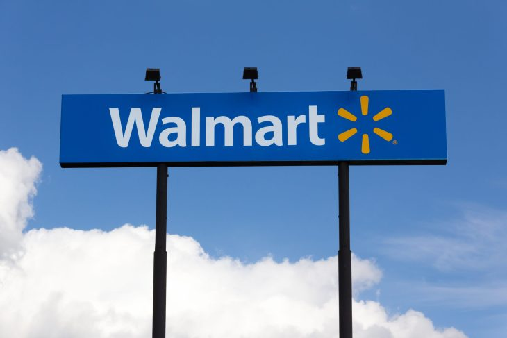 A Walmart billboard sign that is in the clear blue sky.