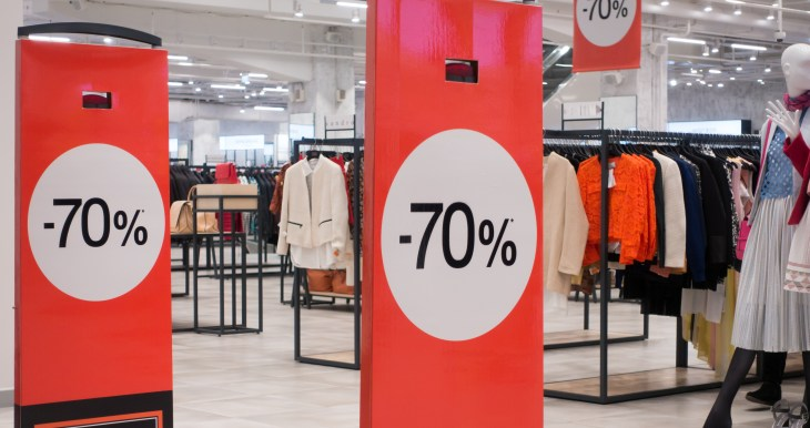 A clothing store with a sale sign.
