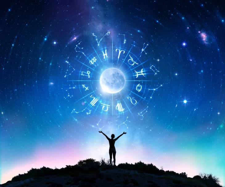 A silhouette of a person standing on a mountain looking above a circle of astronomical signs that is centered by a full moon.