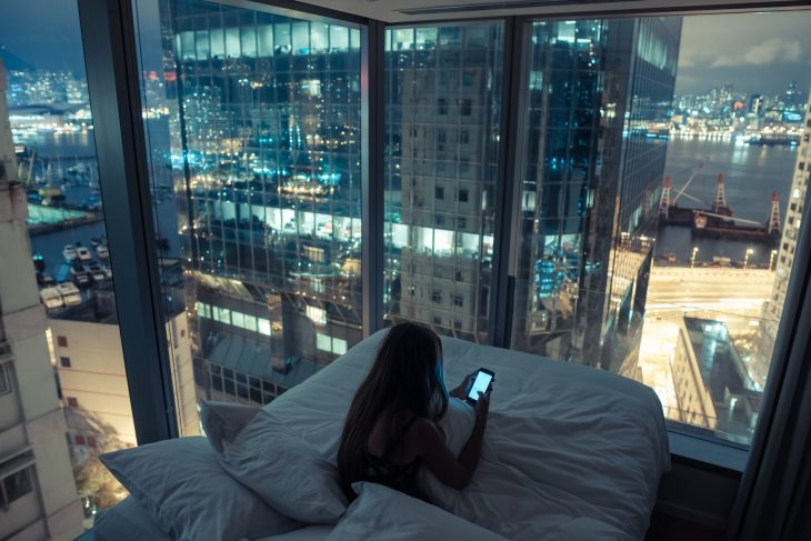 Looking at phone over city view