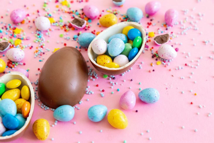 Assorted Easter themed candies and chocolate eggs on pink background