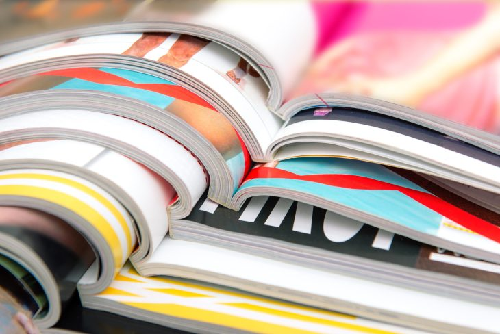 A stack of open fashion magazines