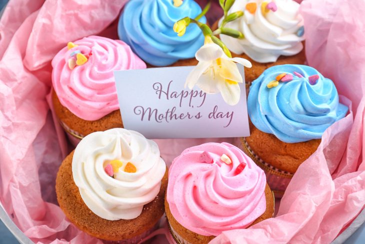 """Basket of cupcakes lined with pink paper and a note reading """"Happy Mother's Day"""""""