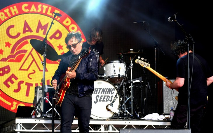 Ian Broudie standing on the stage at Camp Bestival, playing a guitar, on July 30th, 2017
