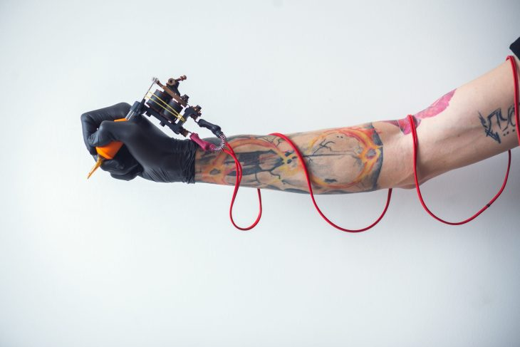 Guy holding tattoo gun with cord wrapped around his arm, only his one arm showing