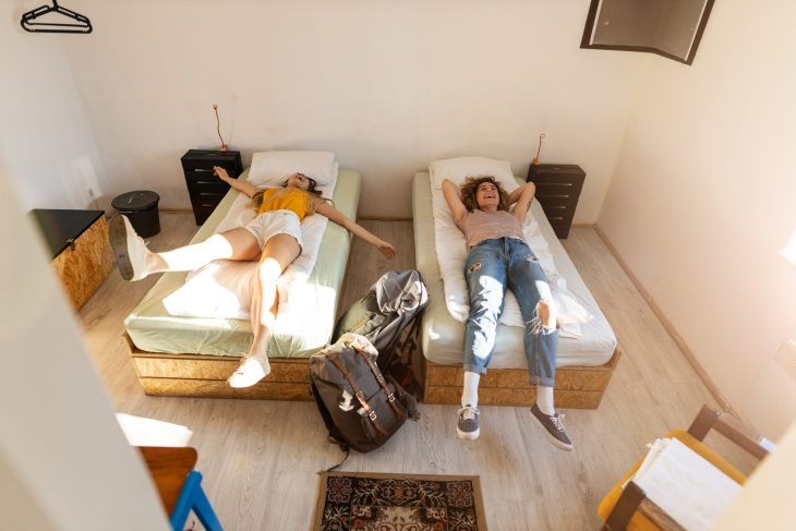 two girls moving into their dorm room, view from above them looking down