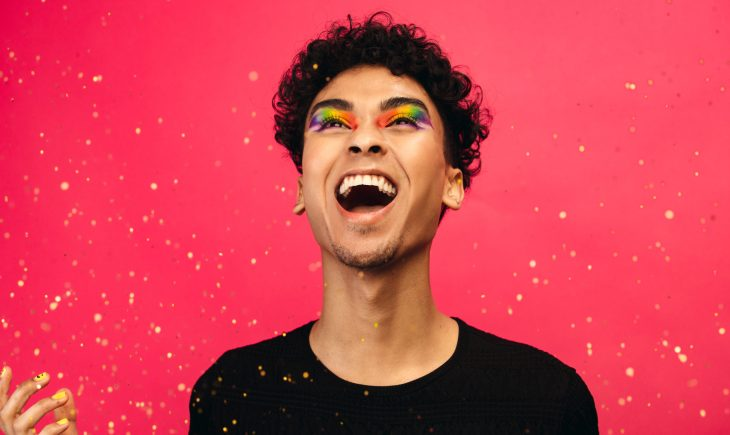 Excited gay man with rainbow makeup and glitter flying