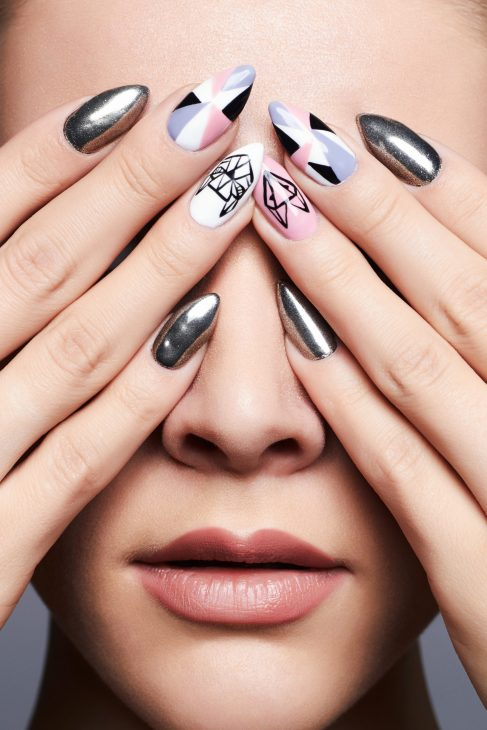 cool nail art on womans finger nails while hands covering her eyes
