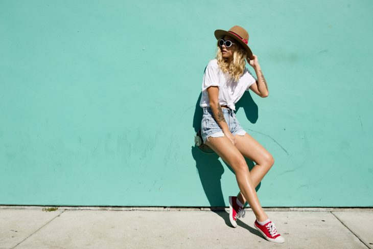cool girl standing in the sun against mint background