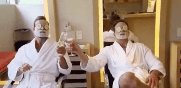 Two guys sitting in robes at a spa cheersing with champagne and cucumbers on their eyes