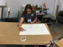 Student draws before she works with water color paint.