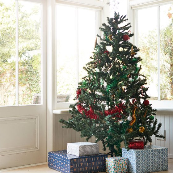 Christmas tree with gift boxes by window at home