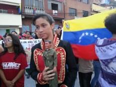 Valeria Fonseca, de 12 años, vestida como Simón Bolívar, porta un muñeco del ex presidente Hugo Chávez en la conmemoración del primer aniversario de su muerte.