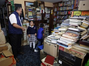 In this Aug. 19, 2015, photo, Jose Alberto Gutierrez, left, talks to children visiting his library at his home in Bogota, Colombia, Wednesday. The reading material slowly piles up, and now the ground floor of his small house is a makeshift community library stacked from floor to ceiling with some 20,000 books, ranging from chemistry textbooks to children's classics. (AP Photo/Fernando Vergara)