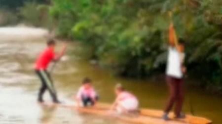 niños en balsa cruzan rio