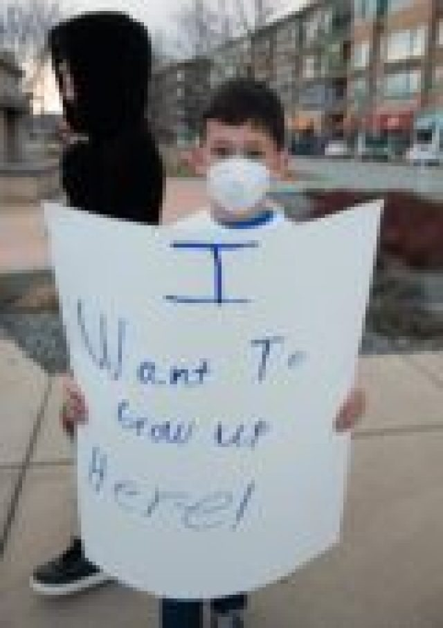 A young protester outside the Broomfield community oil and gas forum on Tuesday, Feb. 21. (Photo by Ted Wood/The Story Group).