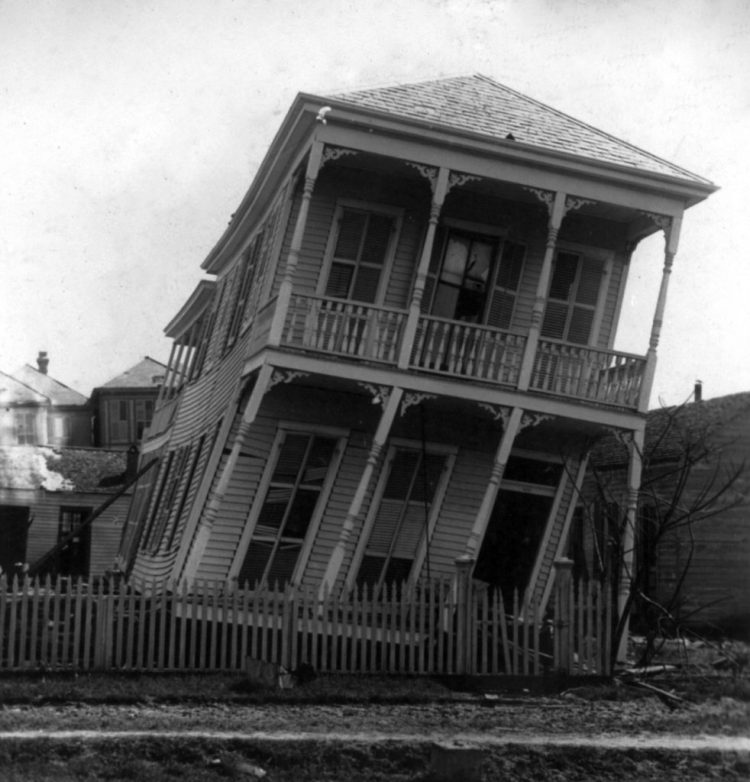 Tilted 2 story house after hurricane. In black and white