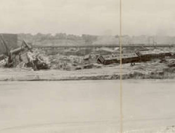 Dreadful flood of Pueblo looking west from Santa Fe Ave.  Panoramic view of wrecked Denver & Rio Grande Western and Missouri Pacific RR freight cars, passenger cars & a locomotive in a rail yard, June 3, 1921.