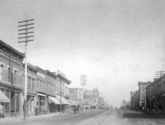 View of Santa Fe Avenue with large electric utility poles.  A horse-drawn wagon and railway tracks are in the street, 1890s.