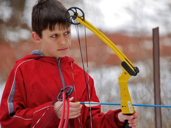 The look of determination! A young boy aims at a bear target on the 3-D range. Photo by Jerry Neal/CPW.