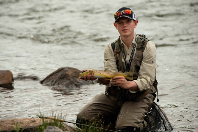 Joseph Speirs of Team Ireland with a brown trout caught on the Colorado River.  Photo by Mike DelliVeneri/CPW.