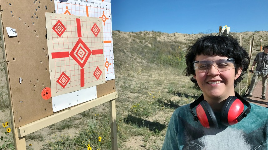 Natalie poses with her target after large-bore shooting practice.