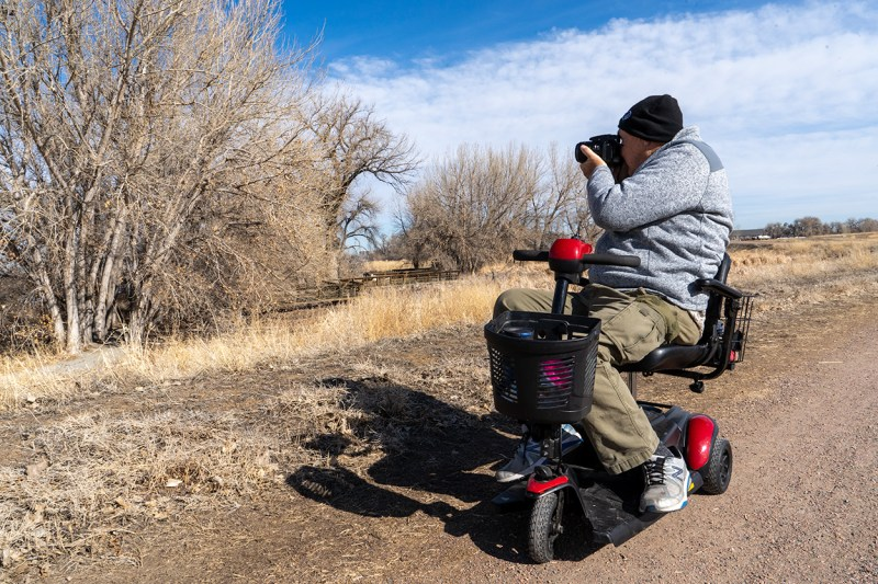 A park visitor takes advantage of the hardpack dirt and gravel trails to do some sightseeing and photography from a mobility scooter.