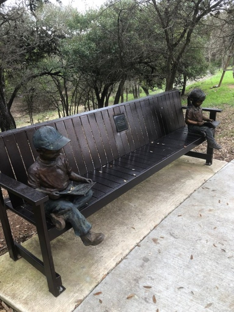 A bench with sculptures on the trail.