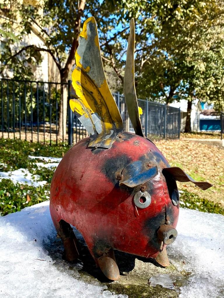 metal sculpture of flying pig