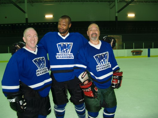 Mustafa, center, with friends at an adult hockey camp. (Rick Parisi, Weekend Warriors Hockey).