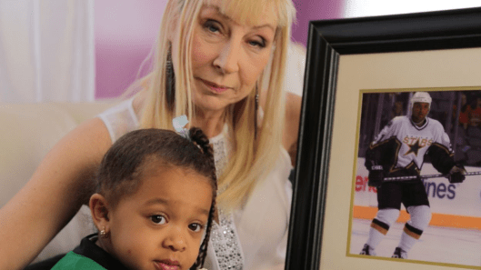 Trudy Daley (right) holds a photo of her son, defenseman Trevor Daley, from his playing days with the Dallas Stars (Photo/Damon Kwame Mason).