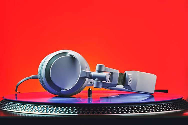 Player turntable vinyl records and white headphones in red light. Equipment for the disc jockey. Sound technology for DJ to mix and play music. Violet vinyl plate. Vinyl turntable in red light