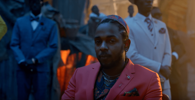 A closeup of Kendrick Lamar sitting in a red tailored suit among brightly-dressed men in a shanty town at sunset.
