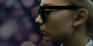 Illustration of Natalie Dormer as Sofia in 'In Darkness.' Behind her is a bokeh-esque background simulating blindness