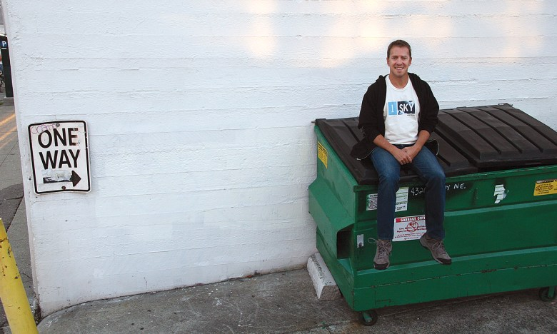 Colin Beavan sits on the top of a recycling bin outside in front of a whitewashed wall.