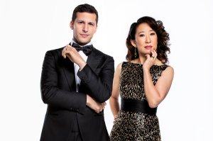 Andy Samberg and Sandra Oh, wearing their black tie best (Samberg in a traditional tux and Oh in a black and gold-tipped dress), pose for a promo shoot for the Golden Globes.