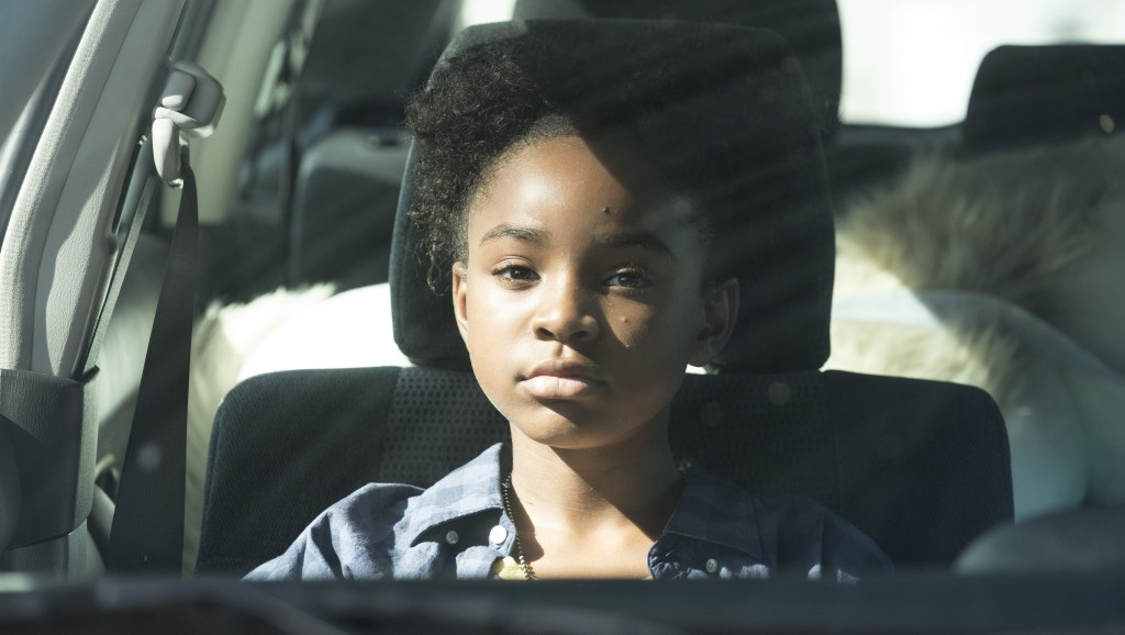Saniyya Sidney as Amy in The Passage. CR: Eliza Morse / FOX. Amy, wearing two afro puffs, a blue buton down shirt with a necklace, is sitting in the front seat of a car, looking stoically at the camera.