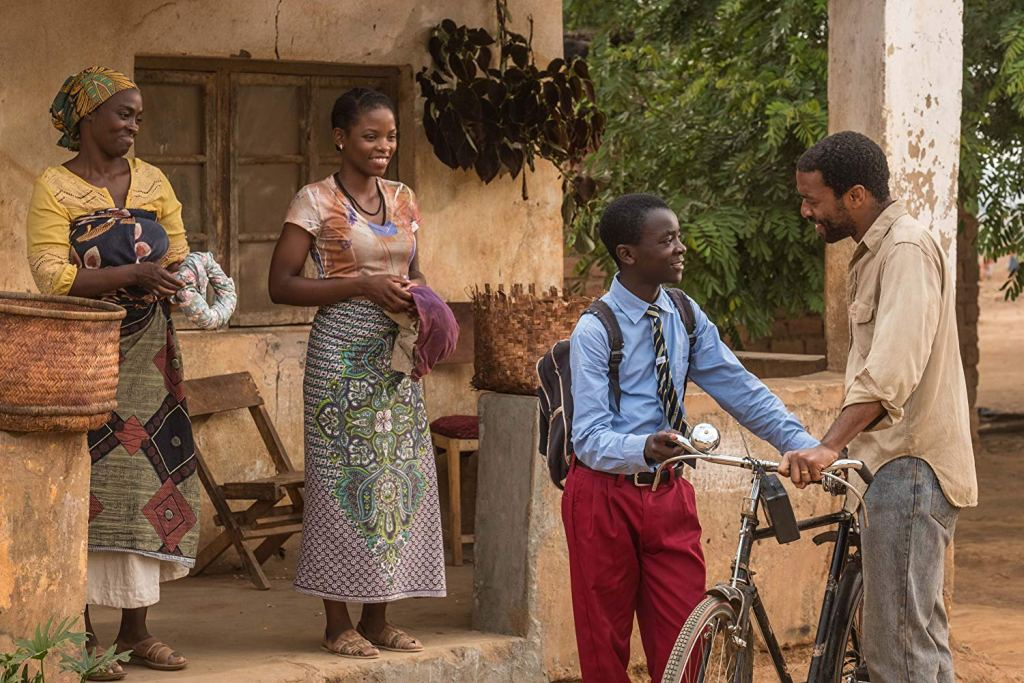 Aïssa Maïga, Lily Banda , Chiwetel Ejiofor and Maxwell Simba (as their characters) are outside their family home in Malawi. The two women are wearing colorful, traditional clothes. Simba is in his school uniform with a grey backpack and school tie. Ejiofor is wearing a khaki shirt and grey jeans. His hand is on his bike.