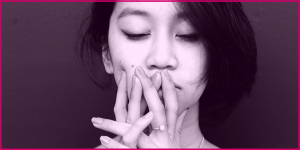 We can fight back against COVID-19 racism. Tinted picture of an Asian woman with her eyes closed and hands over her mouth.